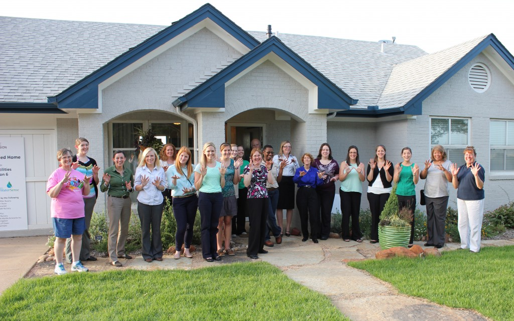 Group photo in front of the Watersense home, doing our best rainfall fingers!